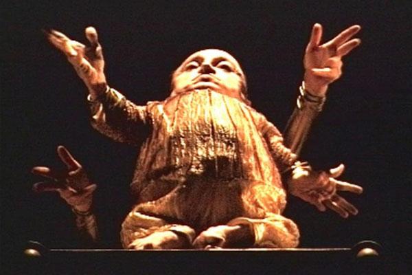 Um homem em um palco com os braços abertos, as mãos espalmadas e com o tronco inclinado para trás. Ele tem o corpo muito pequeno e as pernas atrofiadas. Atrás de seu corpo outras duas mãos compõe a imagem como se o homem tivesse quatro braços. Ele está usando um figurino dourado.