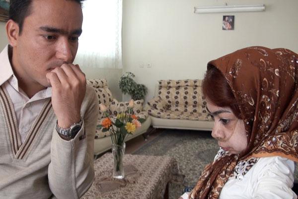 Um homem e uma mulher sentados frente a frente em uma sala. Ela olha para baixo e tem um cateter no nariz. Ele tem cabelos curtos pretos e olha para baixo.