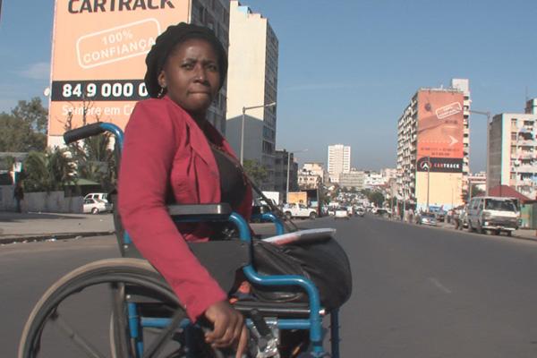 Uma mulher negra em uma cadeira de rodas no meio de uma avenida larga com piso de asfalto. Veste blusa e calças pretas e casaco cor de vinho. Ao fundo, prédios altos, automóveis e o céu azul.