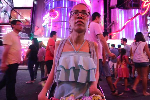 Uma moça em uma rua iluminada e movimentada de noite. Ela está em uma cadeira de rodas e usa vestido azul. Pessoas passam atrás e há letreiros de lojas.