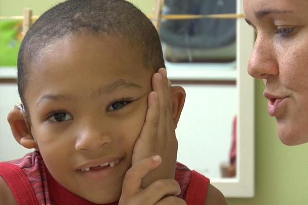 Rosto de um menino olhando para frente e sorrindo. Ele está apoiando a cabeça com a mão esquerda e usa aparelho auditivo. Uma mulher fala próximo ao ouvido dele.