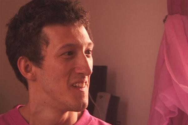 Rosto de um homem jovem sorrindo. Ele tem o rosto magro, pele branca, cabelos castanhos curtos, olhos levemente puxados e usa uma camiseta rosa.
