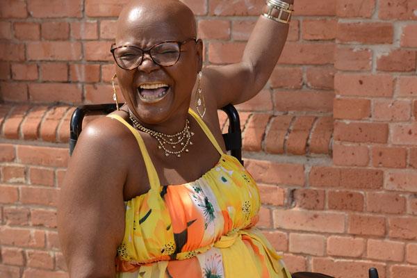 Uma mulher negra em uma cadeira de rodas com um sorriso largo. Ela é calva e usa óculos. Usa vestido amarelo com estampa de flores laranja e bijuterias douradas.