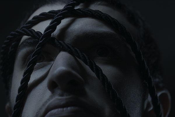 Foto em preto e branco. O rosto de um jovem enroscado com cordas pretas. Ele é branco, tem os cabelos pretos curtos, o nariz fino e pequeno e um leve bigode.