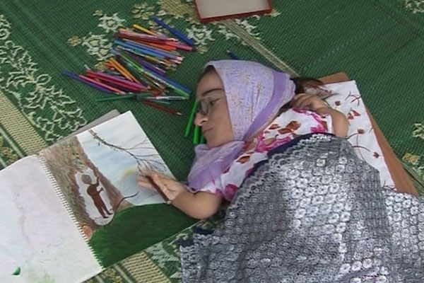 Uma mulher muito pequena está deitada sobre um tapete verde. Usa lenço na cabeça e está coberta com um tecido prateado. Ela faz um desenho com lápis de cor.