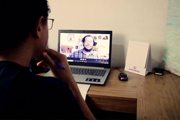 Um homem sentado de costas observa um notebook. Tem os cabelos escuros, curtos, encaracolados e usa óculos. Na tela, imagem de um homem negro de blusa xadrez.