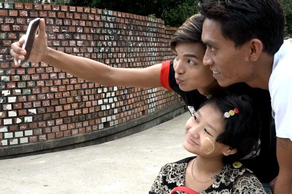 Uma moça segura um celular fazendo uma selfie dela, de um rapaz e de uma menina. Estão com os rostos bem próximos um do outro e olham para o celular sorrindo.