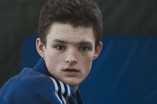 Um jovem de pele muito clara, cabelos curtos lisos na cor castanha, olha em direção a câmera com expressão séria e concentrada. Usa casaco de uniforme na cor azul com três listras brancas na altura do ombro.